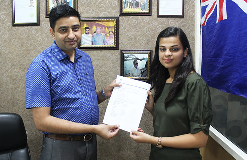 Mr. Gurvinder Kang (Director of West Highlander) handing over Australia Student Visa to Isha Jain