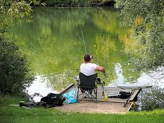 Multi-tasking (Smiffy'37) Tags: lake angler fishing hobby green reflections