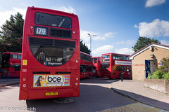 How To Fill A Bus Station (M C Smith) Tags: blue clouds white buses red chingford busstation route 179 97 212 444 building shadows poster letters numbers symbols advertising lamp wall pavement kerb bushes green blockpaving reflections trees railings bollard black yellow