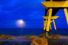 Full moonrise among clouds (Fnikos) Tags: sea water mar mare wave rock pier bridge puente pont construction sky cloud moon moonrise skyline seascape evening night nightview nightshot badalona bay outdoor