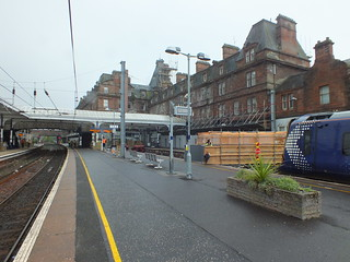 380005 sits in the shortened platform in Ayr whilst the station hotel in the background has a decision made on its future