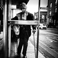 Soon (Kieron Ellis) Tags: man old oldman cane stick busstop pavement road car glasses bag street candid blackandwhite blackwhite monochrome reflection glass
