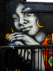 That Certain Smile (Steve Taylor (Photography)) Tags: gold hoops earrings diamond art graffiti portrait mural streetart black orange grey blue red uk england london camden gb greatbritain woman lady face head hands railing