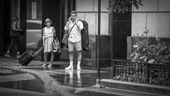 The Call..... (Kevin Povenz Thanks for all the views and comments) Tags: 2018 july kevin kevinpovenz illinios chicago windycity street streetphotography people male man female woman blackandwhite bw canon7dmarkii sigma24105art wet rain phone shorts wrinkled wrinkle luggage white whiteshirt