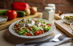 Dramatic Greek (Syncher) Tags: salad dramatic lighting restaurant dish cutting boards salt pepper vegetables brick wood board table cutlery sauce feta tomato tomatoe chickpea menu d600 50mm sigma