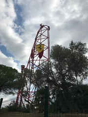 030 - Rollercoaster (EllieSmithPhotos) Tags: clouds cloudy grey white summer sunny sun holiday rollercoaster spain portaventura tourists visitors riders carts red ferrari yellow black tall huge trees green greenery man manmade photo photography photograph image imagery picture