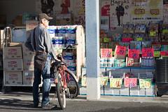 Man on bike by discount store, Nara, Japan (mistermacrophotos) Tags: man sunglasses shades cool discount shop wares display streetscene hat stare canon 5d mk4 bicycle bag low sun explore explored shopping bike japan nara asia attitude