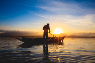 Silhouette fisherman standing in the boat during sunrise
