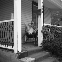 untitled (kaumpphoto) Tags: rolleiflex 120 tlr ilford bw black white porch sit read book recline chair street minneapolis railing steps stairs home relax straw stipe drink mail foot number box