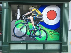 Tour of Britain. Cafe window with mural and odd comment. (Bennydorm) Tags: yearly annually bici velo current topical painting yellowjersey urban inglaterra inghilterra angleterre europe uk gb britain england cumbria furness ulverston art artwork iphone6s words comment cyclist window colourful cafe mural roundel wheels cycle bicycle bike racer roadrace cycling tourofbritain