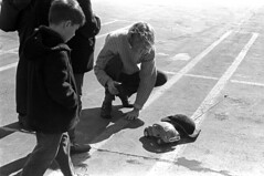 020571 36 (ndpa / s. lundeen, archivist) Tags: nick dewolf nickdewolf blackwhite blackandwhite 35mm film bw february 1971 1970s boston massachusetts cambridge lechmere lechmeresales firststreet parkinglot photographbynickdewolf man child boy quentin nd car modelcar rccar rc radiocontrolled vw volkswagen bug beetle blond blonde longhair controller antenna