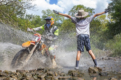 Soaked (Kyle William Russell) Tags: motocross moto motorcycle harescramble scramble splash water sky clouds orange green kid child youth wet ktm race racing drops trees stream rocks