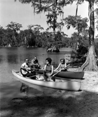 Couples with canoes on shore - Wakulla Springs (State Library and Archives of Florida) Tags: florida wakullasprings canoes couples guitars
