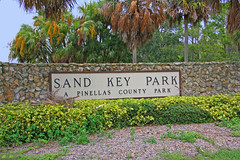 Entrance to Sand Key Park, Clearwater, Florida (1 of 2) (gg1electrice60) Tags: sandkey sandkeypark park beach shoreline gulfofmexico barrierisland sandbar intercoastalwaterway clearwatercommunitysailingcenter sailingcenter clearwater florida fl unitedstates usa us pinellascounty america gulfboulevard gulfblvd parkentrance nearfirestation44 1001gulfboulevard 1001gulfblvd countyroad183 cr183 countyrd183 stateroad699 sr699 staterd699 floridaroad699 signs billboard plaque rockwall shrubs palmtress vegetation
