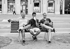 Taking a break. (susanjanegolding) Tags: canon friends speaknoevil hearnoevil seenoevil camera cellphone switzerland swiss tourism tourists straw phone bench lucerne luzern men man drink father son monochrome blackandwhite adultchildren fujifilmxpro2