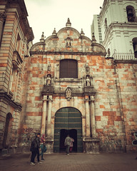 A classic church facade in Bogotá, Colombia. (pedferr) Tags: ancient color historic church retro moody southamerica 4x5 decorative door morning catholic architecture colombia dramatic stone building old people vertical facade aged religion exterior window classic wall travel vintage trip streetphotography front sky city god antique