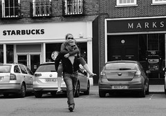 Slipping off the Piggy Back (Bury Gardener) Tags: nikond7200 nikon england britain 2018 snaps eastanglia uk suffolk streetphotography street streetcandids strangers candid candids people peoplewatching folks blackandwhite bw buttermarket