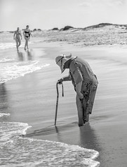 Woman at the Beach (crabsandbeer (Kevin Moore)) Tags: oc assateague beach easternshore maryland ocean people trip tugboat woman girls age oldage aging juxtaposition surf street candid portrait sand sinking cane oldwoman youth life contrast bw monochrome blackandwhite