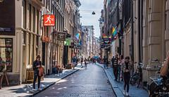2018 - Amsterdam - Warmoesstraat (Ted's photos - For Me & You) Tags: 2018 amsterdam cropped nikon nikond750 nikonfx tedmcgrath tedsphotos vignetting flag flags streetscene street shadow shadows people peopleandpaths pathsandpeople buildings rainbowflag ypical scene