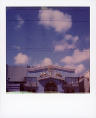Perfect Blue Buildings (tobysx70) Tags: polaroid originals color 600 instant film slr680 perfect blue buildings kadampa meditation center 17th street mission district san francisco california ca buddha buddhism buddhist gold dharmachakra dharma wheel eight 8 spokes deer sky clouds door counting crows song lyrics polawalk polavacation 042718 toby hancock photography