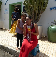 Lady in Red (metrogogo) Tags: ladyinred reddress cooldrink lanzarote teguise red yellowskirt cactus straw green lady barefooted