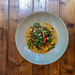 Top view of organic tofu with coconut curry with oyster mushroom, bush beans, baby eggplant, cherry tomatoes, with ribbon noodles, peanuts, fried onions and herbs
