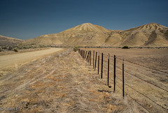 The Road Less Traveled (nebulous 1) Tags: ca newidria road clear desolate dirtroad fence hills landscape lesstraveled lesstaken