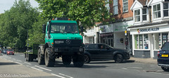 Unimog (M C Smith) Tags: epping town shops pavement unimog green pentax k3 trees parkingspaces cars black orange lights shadows crossing trailer signs yellow lines white letters numbers symbols woman man