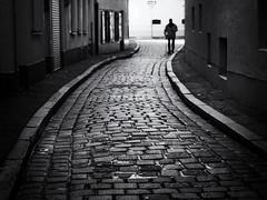 slowly (Sandy...J) Tags: olympus atmosphere atmosphäre alone allein augsburg walking blackwhite bw city cobblestones urban noir street streetphotography sw schwarzweis strasenfotografie stadt silhouette shadow light monochrom man mann strase mood stimmung