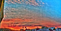 Sunset Noir Panorama (Walker Dukes) Tags: orange red clouds blue sky urban vista view light rays lightrays palm trees