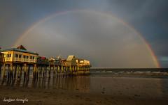 Chasing Rainbows (Christina DeAngelo) Tags: rainbow rain sunny beach surf coast ocean sea pier wharf shops sky landscape seascape oldorchardbeach maine