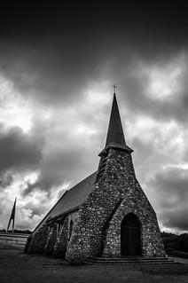 Moody fine art black & white combining La Chapelle Notre Dame de la Garde and the monument The White Bird (L'Oiseau Blanc) at the top of the cliffs - Falaise d'Amont, Etretat, Seine-Maritime, Normandy, France