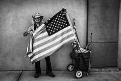 the flag belongs to people (jrockar) Tags: portrait streetportrait street streetphoto aboutstreet streetphotography documentary photography decisive moment instant jrockar janrockar idiot ordinarymadness ordinary madness bw mono blackandwhite flag us usa fuji fujifilm x100s man guy oakland cowboy life people