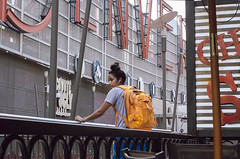 Waiting (adrianmichaelphotography) Tags: female woman airpods girl yellow backpack denver street streetphotographer streetphotography ricoh isolation downtowndenver