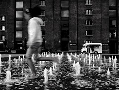 Fountains (mesbkr1) Tags: canonphotography canon londonstreets running centralstmartins people london bnw kingscross streetphotography photography blackandwhite motion street fountain water
