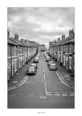 Terraced Street (AnthonyCNeill) Tags: terrace terraced houses street strase rue calle british english road housing parked cars roofs chimneys pavement sidewalk black white bw noir blanc blanco negro schwarz weiss mono monochrome fuji fujifilm acros häuser urban urbano