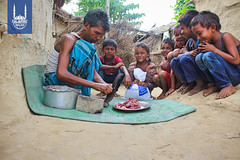 A family preparing Qurbani meat in Nepal, as children wait excitedly to have their meal of meat
