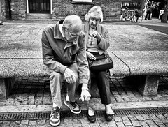 Footsore (Neil. Moralee) Tags: neilmoralee man woman couple married pair foot sore tired footsore sitting shopping feet massage touch rub hold shoes lady neil moralee olympus omd em5 candid cobbles weary exhausted old mature pensioners street black white bw bandw blackandwhite mono monochrome art artistic reportage still life taunton somerset uk england britain glasses love devotion help