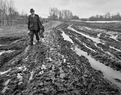 The teacher on a way home (valerii reshetniak) Tags: bw blackandwhite social past historic ukraine valeriireshetniak teacher man walking rain earth mud tracks road life