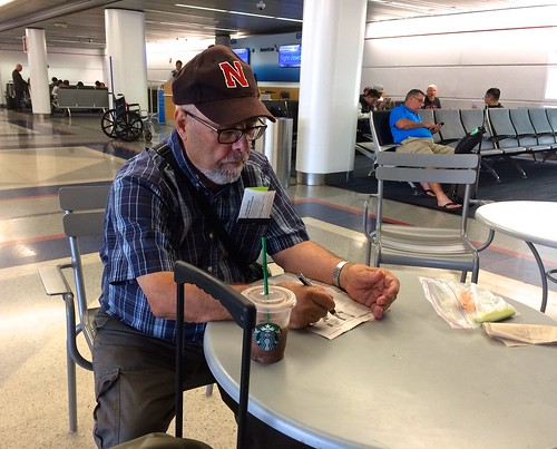 Ali doing a crossword puzzle at O'Hare airport, Photo by CRudin