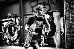 Chewing gum, taking names (Kieron Ellis) Tags: man hat skateboard baseballhat watch tattoo graffiti walking wall backpack teeshirt chewinggum candid street blackandwhite blackwhite monochrome