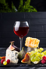 Grape, cheese, figs and honey with a glasses of red on a stone black background over brick black wall with green flower, copy space (lyule4ik) Tags: cheese wine grape board food french red glass delicatessen gourmet appetizer snack background white italian wood fruit bottle alcohol dairy wooden plate france table brie camembert drink product various wineglass walnut dinner party yellow beverage goat holiday meal parmesan restaurant sweet assorted honey nut cuisine bordeaux vine autumn tasty art