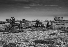 Dungeness Landscape (3)-03271 (G.K.Jnr.) Tags: landscape seascape historic foliage vegetation boat transport deserted desolate discarded dilapidation water seas seaside coastline beach shingle outdoor sky scenic interest touristattraction monochrome bw blackandwhite blackwhitephotos rural dungeness romneymarsh kent unitedkingdom fujix apsc xh1 building winch machinery wood