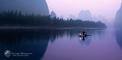 Fisherman with the lantern at the middle of the Li river (Victoria_Rogotneva) Tags: china chinese guangxi kasahat theliriver unitravels victoriarogotneva viktoriarogotneva xingpingtown yangshuo asia beard bird boat fisherman fishnets karstmountains lamp landscape lantern man mountains nets panorama phototour reflection rock sunrise view