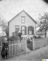 tm_5436 (Tidaholms Museum) Tags: svartvit positiv gruppfoto människor byggnad exteriör bostadshus trädgård usa hund staket