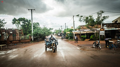 African Transportation (BeyondThePrism) Tags: red rural road wet rain motorist motorcycle transport travel africa african sky color colourful beyondtheprism beyond wwwbeyondtheprismcom prism castonguay castonguayjeanphilippe jpcastonguay jpc fuji fujifilm fuj fujix70 x70 mirrorless