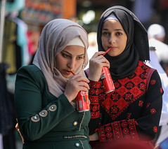 Our world becomes flat, and the taste of life tasteless (ybiberman) Tags: israel jerusalem oldcity alquds muslimquarter damascusgate girls adolescent people hijab cocacola drink straw red candid streetphotography
