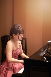 Young female musician playing piano in concert hall