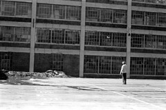 020571 15 (ndpa / s. lundeen, archivist) Tags: nick dewolf nickdewolf blackwhite blackandwhite 35mm film bw february 1971 1970s boston massachusetts cambridge lechmere lechmeresales firststreet parkinglot photographbynickdewolf building windows snow meltingsnow man nd flying plane airplane modelplane modelairplane