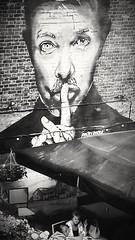 Keep the noise down.... (markwilkins64) Tags: markwilkins hangingbasket humour brickwall bricks wall cafe streetstory candid streetphotography street mural monochrome mono blackandwhite claphamjunction clapham london